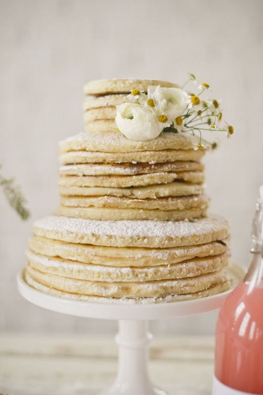 a pancake wedding cake with sugar powder and fresh white blooms is a fab idea for a modern laid back wedding