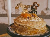 a delicious crepe wedding cake with fresh fruits, cream and nuts on top plus a gold cake topper is a lovely idea for a homey and cozy wedding