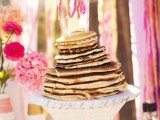 a pancake wedding cake with a pink bunting cake topper is a lovely idea for a relaxed and colorful wedding in spring or summer