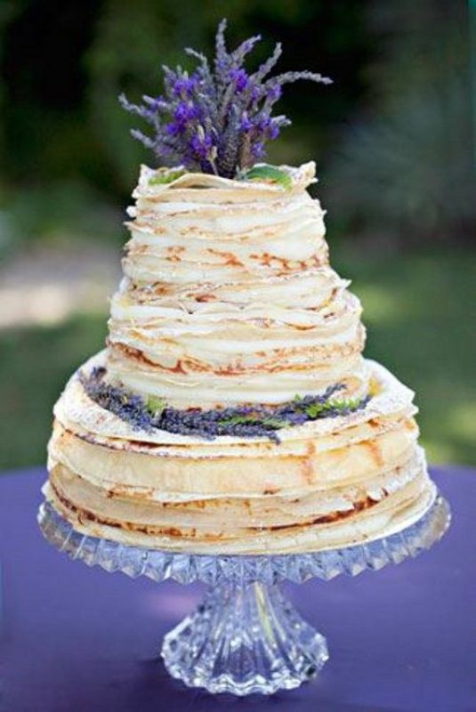 a crepe wedding cake topped with lavender and with cream between tiers is a gorgeous idea for any wedding