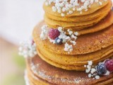 a pancake wedding cake topped with baby's breath, berries and sugar powder is a gorgeous idea for a relaxed summer wedding