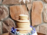 a classy pancake wedding cake with caramel in between, with fresh blooms and a bunting cake topper for a rustic wedding