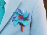 a light blue suit, a white shirt, a turquoise tie and a bright paper boutonniere for a fun touch