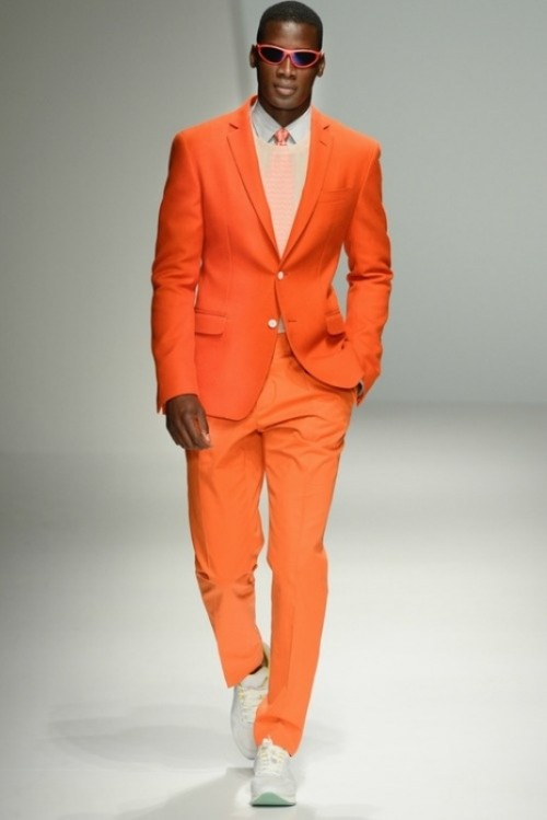 a bright orange suit, a white shirt, a bright orange tie and white sneakers for a bold and chic modern groom's look