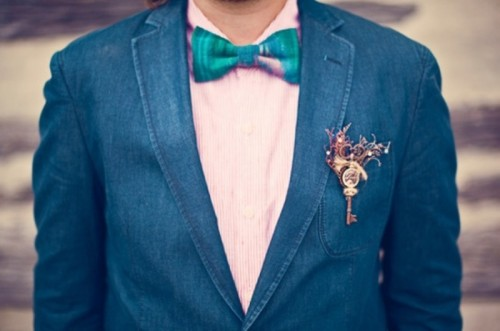 a navy suit, a pink printed shirt, a bright turquoise bow tie and a steampunk boutonniere with a vintage key