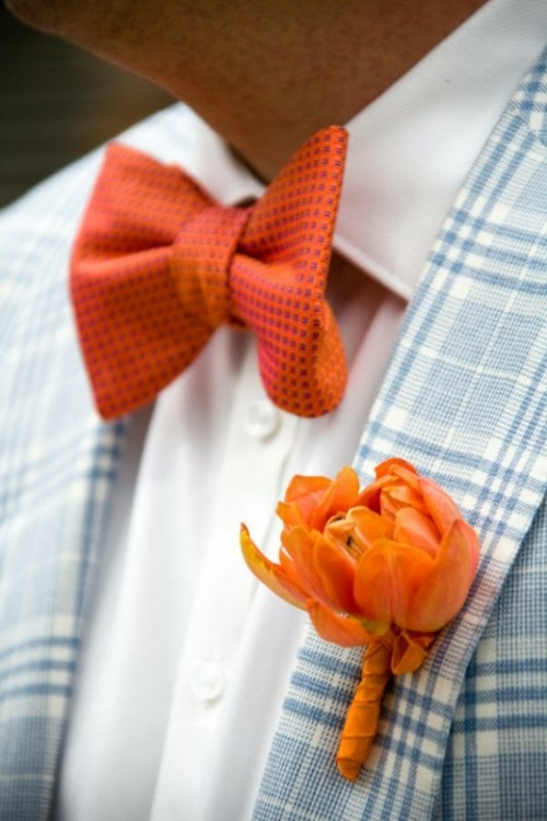 a light blue plaid blazer accented with an orange floral boutonniere and a matching bow tie for a contrast