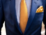 a navy suit, a printed blue shirt and a bright yellow tie and handkerchief for a bold and fun look