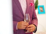 a purple suit, a printed pink shirt, a brigth pink bow tie and a matching handkerchief