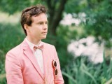 a pastel pink suit, a white shirt and a pink printed bow tie for a light and fun summer groom's look