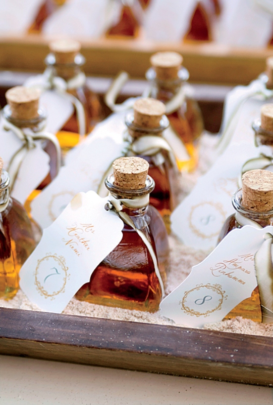 mini whiskey bottles with tags are cool wedding escort cards and cool drinkable wedding favors at the same time