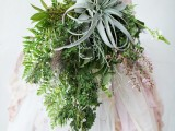 a unique wedding bouquet with textural cascading greenery, some blooming branches and a large air plant