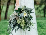 a textural and catchy greenery wedding bouquet including various types of eucalyptus and large white blooms and herbs