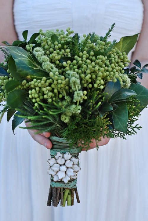 a textural wedding bouquet with large leaves and some berries and an embellished bouquet handle for a cool look