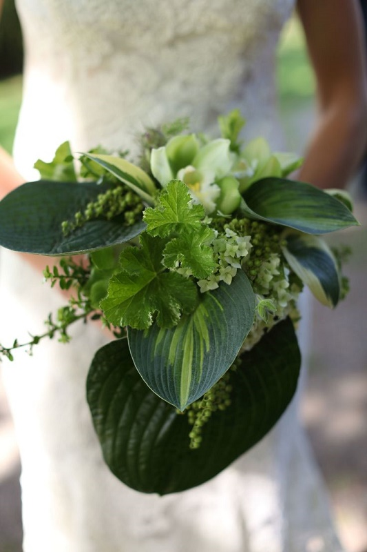 a greenery wedding bouquet with lush leaves, greenery, some white blooms looks very chic and very bold