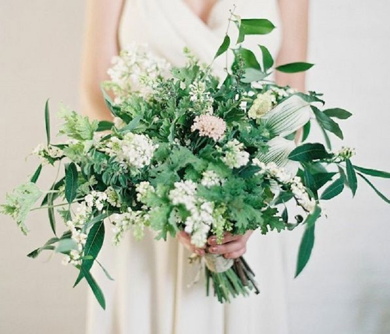 a lush textural greenery wedding bouquet with soem white and pink blooms for a more eye catching look