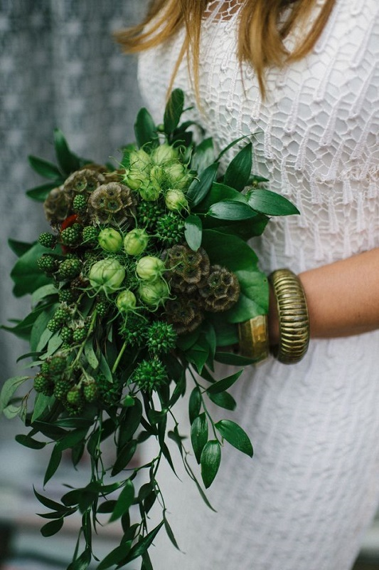 a cascading greenery wedding bouquet with lush leaves, berries and seed pods is a cool idea for a spring or summer wedding