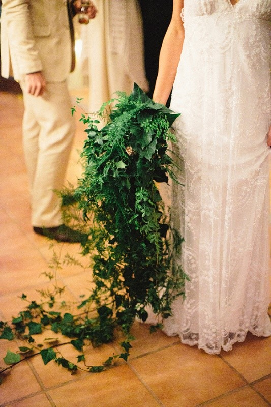 a veyr lush cascading greenery wedding bouquet with lots of various types of greenery going down to the floor