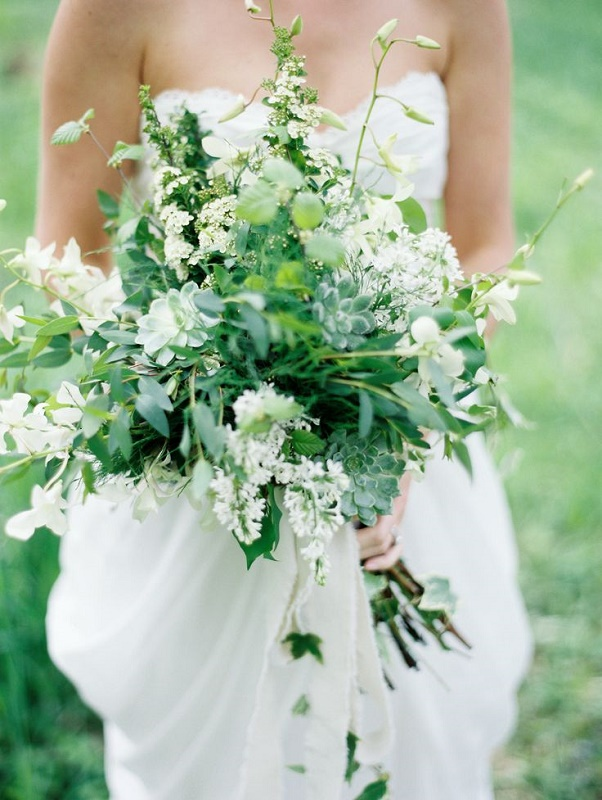 a very lush and textural greenery wedding bouquet with lots of greenery, succulents and white flowers is a cool and fresh idea