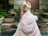 a romantic and refined wedding ballgown in blush, with a draped bodice and a skirt plus thick straps and a train is very exquisite