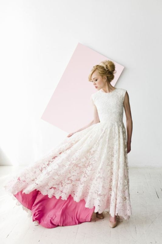 a modern romantic lace A line wedding dress with a high low skirt, a high neckline, no sleeves and a pink underskirt is wow