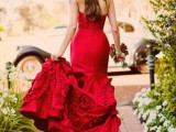 a strapless red mermaid wedding dress with a floral skirt and a train will make a statement with its color and design