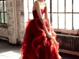 a red strapless wedding dress with a draped bodice and a layered and ruffled skirt is a bold and modern option to rock