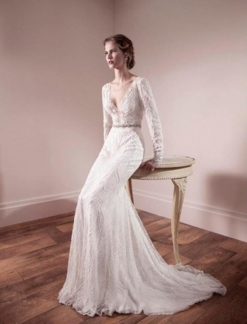 a romantic lace sheath wedding dress with a plunging neckline, long sleeves and an embellished sash