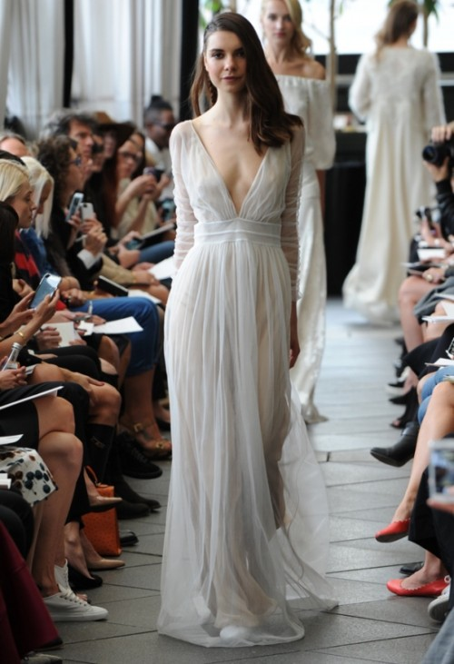 a flowy and airy wedding dress with a draped bodice, long sleeves and a plunging neckline