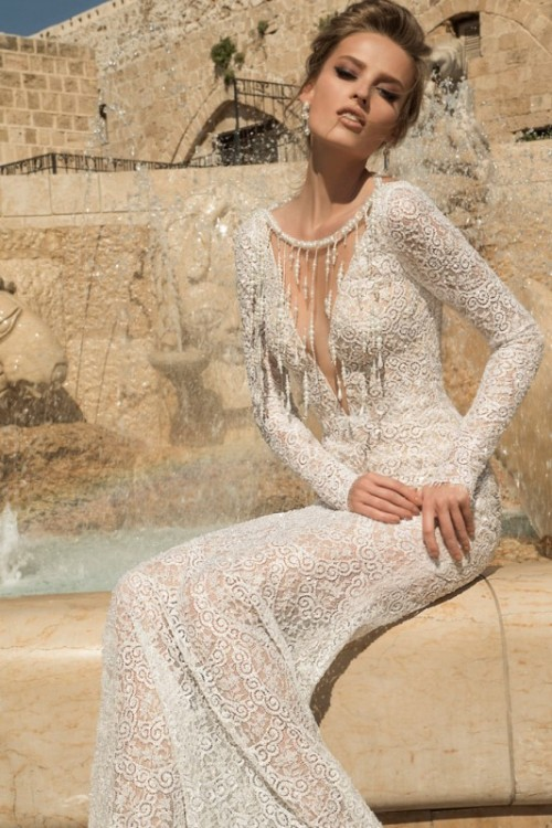 a lace sheath wedding dress with a plunging neckline, long sleeves and a decorative collar with fringe