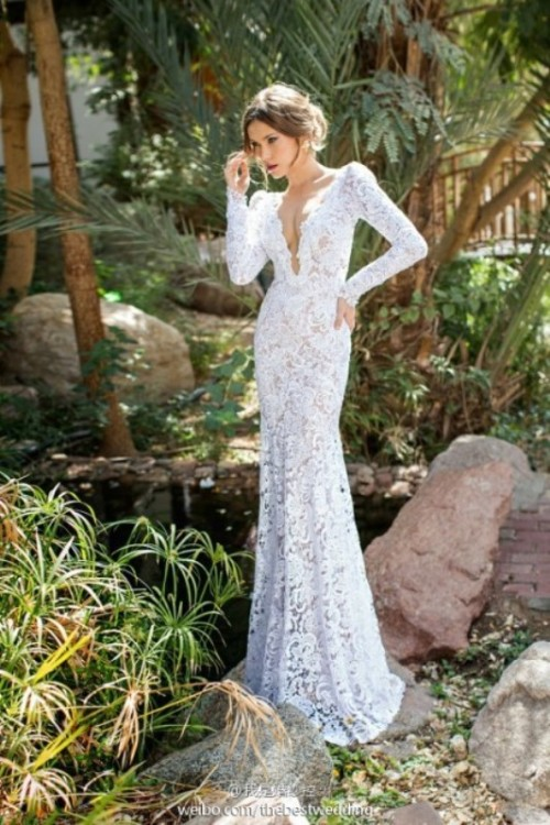 a lace sheath wedding dress with a plunging neckline and long sleeves is very sexy