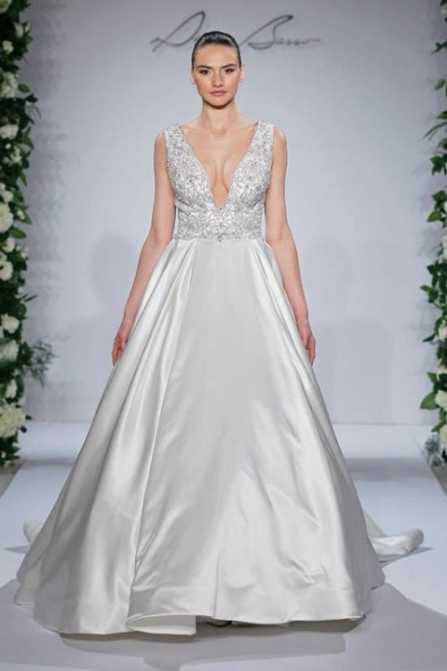 an A-line wedding dress with a lace embellished bodice with a plunging neckline and a plain maxi skirt