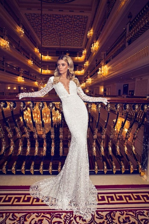 a lace sheath wedding dress with long sleeves and a plunging neckline plus a train is very romantic