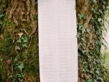 a stylish seating chart of a long paper stripe attached to a tree is a very chic and cool idea for a woodland or fantasy wedding