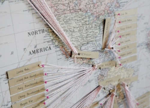 a map seating chart with twine, pins and tags is a stylish and cool modern idea for a travel-loving couple