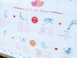 a pastel marine-inspired wedding seating chart with various sea creatures is a cool idea for a beach or coastal wedding