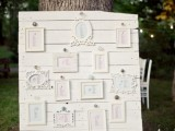 a vintage wedding seating chart in white with an arrangement of various refined frames is an elegant idea