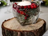a rustic winter wedding centerpiece of a wood slice, a jar with cranberry and evergreens plus a floating candle