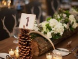 a rustic winter wedding centerpiece of a tree stump with white blooms and greenery, antlers and a pinecone table number