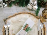 a beautiful winter place setting with an evergreen and pinecone runner, a wood slcie placemats and a cinnamon and evergreen napkin ring