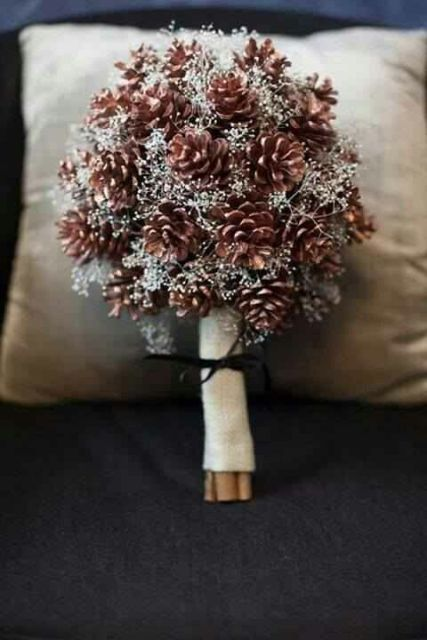 a rustic winter wedding bouquet of pinecones and little white blooms in a burlap wrap is ideal for a rustic bride