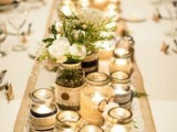 a rustic winter wedding centerpiece of jars with candles and jars with blooms and greenery