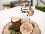 a rustic winter wedding centerpiece of a wood slice, moss, a tree stump and a candle in a candleholder wrapped with twine