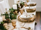 a rustic winter wedding table with an evergreen and pinecone runner, wood slice placemats, candles and colored glasses