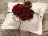 a rustic ring pillow of white burlap, with fabric flowers, pinecones and a wooden heart