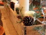 a cozy rustic winter centerpiece of a wooden box filled with pinecones, candles and evergreens is a very easy DIY