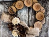 a rustic wood slice wreath with burlap, twigs and fabric blooms is a cool decoration for Christmas and winter weddings