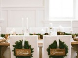 mark your wedding chairs with evergreen wreaths and wooden signs instead of usual signage