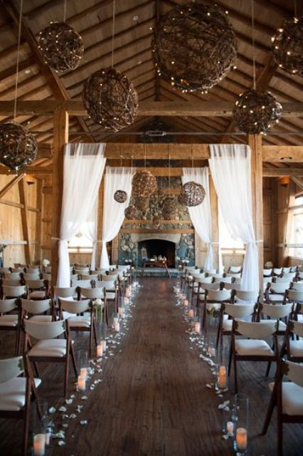 a rustic winter wedding space with yarn and light balls, candles on the floor and a large and cozy fireplace