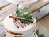a naked wedding cake topped with evergreens and cinnamon sticks is amazing for a rustic winter wedding