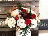 a rustic winter wedding centerpiece of a white jar, white and red blooms including fabric ones, pinecones and greenery